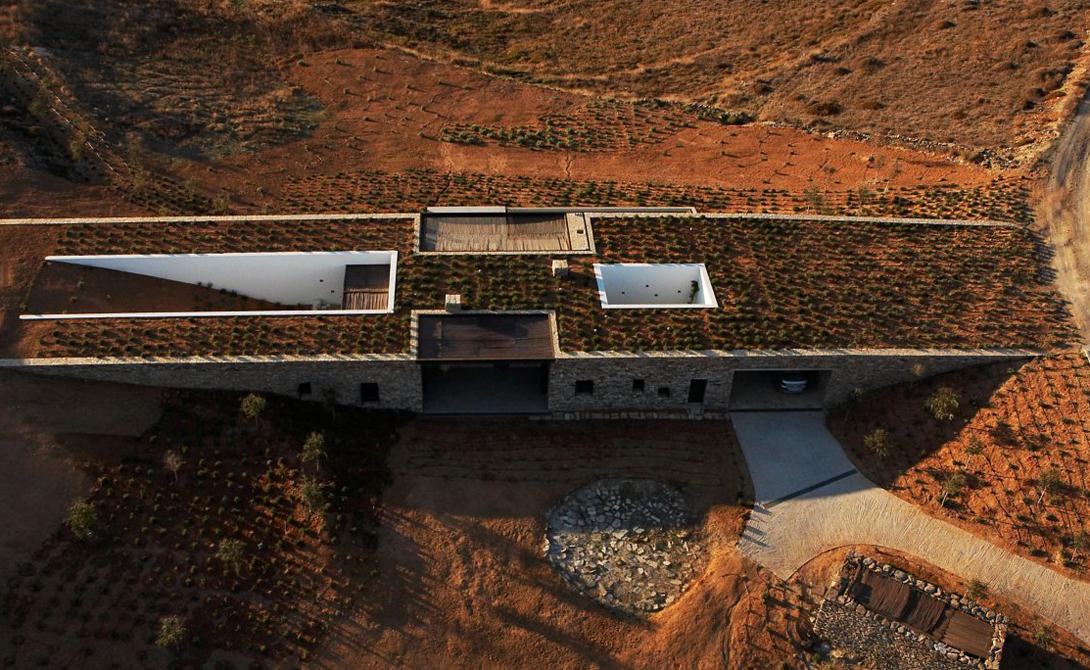 Частный дом на греческом острове Антипароса построен на стыке двух склонов. Длинные каменные стены позволяют ему естественным образом вписаться в окружающее пространство.