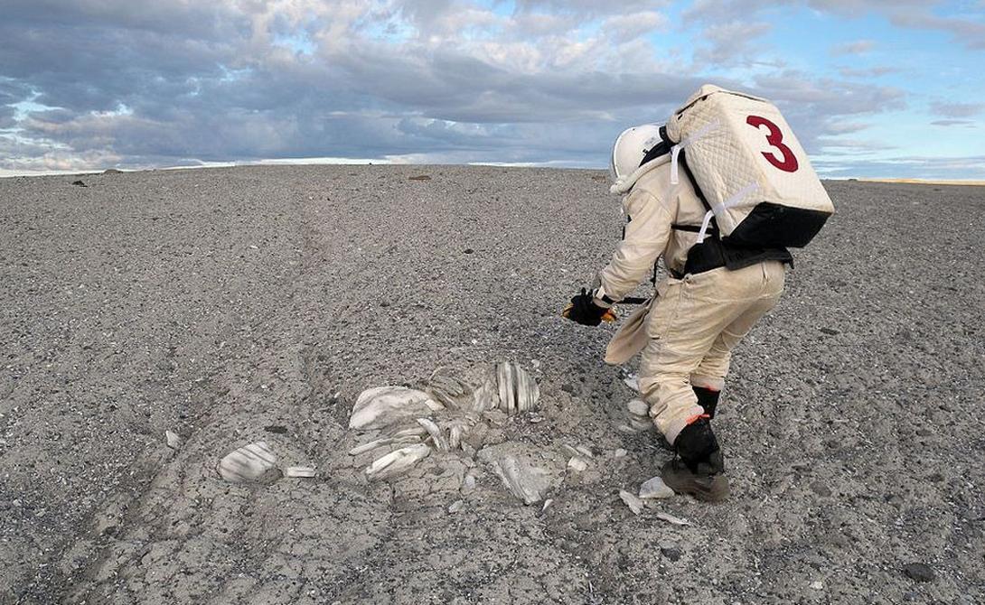 Исследователь в скафандре берет пробы из месторождения ценных минералов на равнине Джемини Хиллс