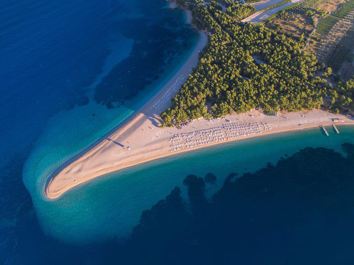 Zlatni Rat Брач, Хорватия Длинный язык песчаного пляжа на хорватском островке Брач выходит далеко в море. Белая галька покрывает практически всю территорию острова, а несколько средиземноморских сосновых рощ обеспечивают отдыхающим достаточное количество тени.
