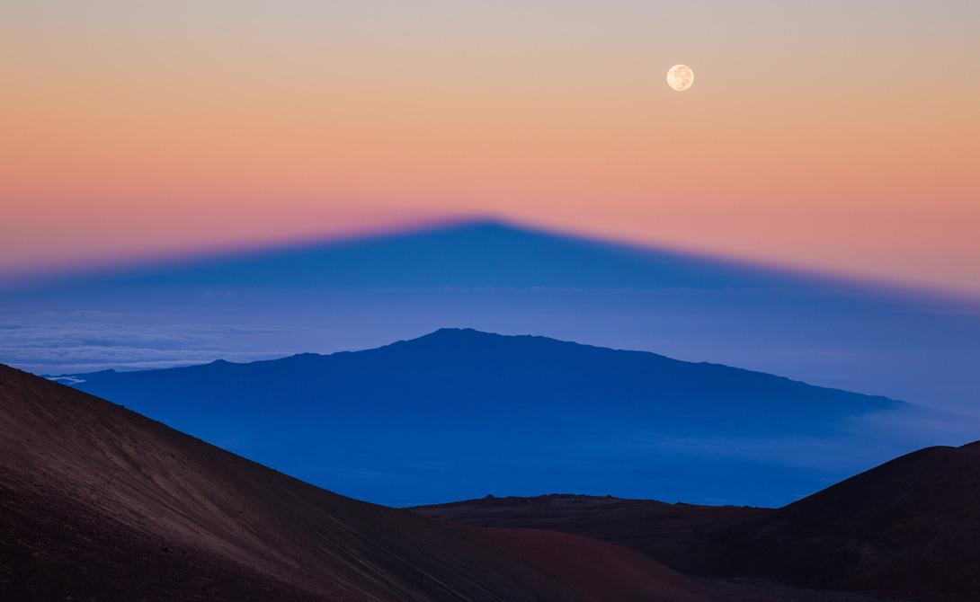 Параллельные горы Тень Мануа Кеа, самого высокого пика на Гавайях, удваивается восходящим над вулканом солнцем.