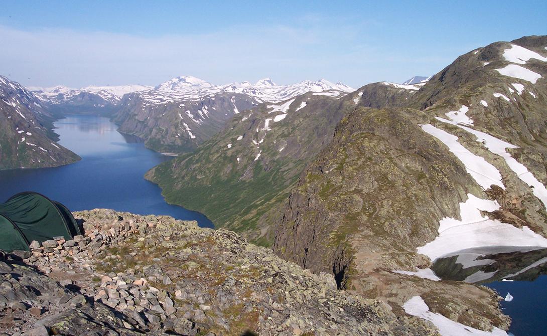 Йотунхеймен Норвегия Норвежский Йотунхеймен известен и под другим именем — туристы и местные предпочитают называть его «Землей гигантов». Тут, среди двух сотен гор, и в самом деле могло бы с комфортом разместиться целое великанье племя. Сказочный пейзаж дополняется ярко-голубыми озерами, наполненными талой водой.