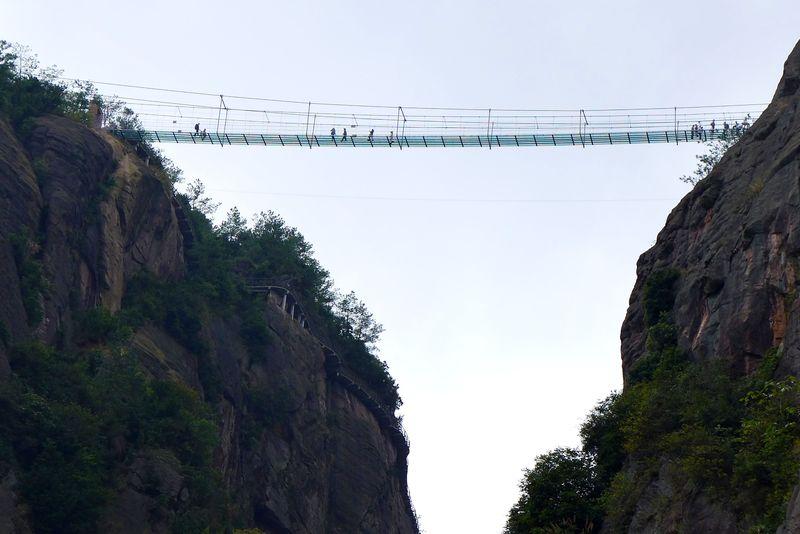 Не смотри вниз Весь аттракцион носит название The Coiling Dragon Cliff Skywalk. Туристы, посещающие гору Тяньмэнь в национальном парке Чжанцзяцзе, пересекают пропасть по мосту длиной в сто метров и шириной всего в два. Эта стеклянная, кажущаяся очень непрочной конструкция единственное, что отделяет человека от глубочайшей пропасти.