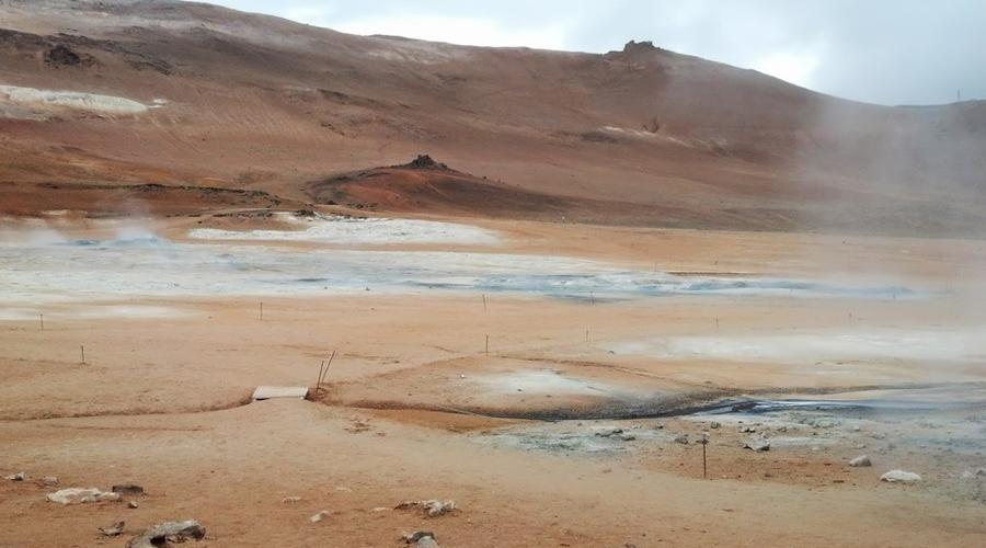 Námaskarð Исландия Если вы когда-либо мечтали гулять по бесплодным пустыням Марса — отправляйтесь к северной части Исландии. Здесь расположено настоящее геотермальное чудо: черные от серной грязи реки прорезают ландшафт, радующий глаз красочными минералами.