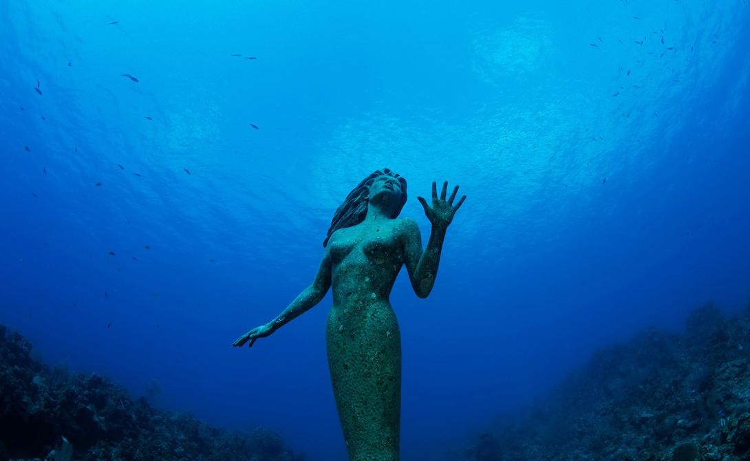 Статуя Амфитриты Каймановы острова Если вы когда-нибудь мечтали повстречать настоящую русалку, то следующий отпуск стоит провести на Большом Каймане. Одна из главных достопримечательностей острова — это статуя русалки, установленная на глубине около 6 метров.