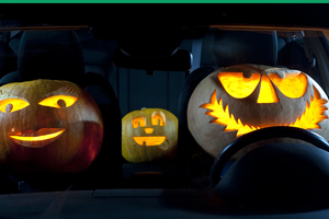 A family of three jack o' lantern pumpkins sitting in a car at night.