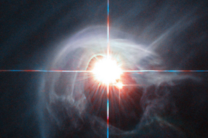 Two stars shine through the centre of a ring of cascading dust in this image taken by the NASA/ESA Hubble Space Telescope. The star system is named DI Cha, and while only two stars are apparent, it is actually a quadruple system containing two sets of binary stars. As this is a relatively young star system it is surrounded by dust. The young stars are moulding the dust into a wispy wrap. The host of this alluring interaction between dust and star is the Chamaeleon I dark cloud — one of three such clouds that comprise a large star-forming region known as the Chamaeleon Complex. DI Cha's juvenility is not remarkable within this region. In fact, the entire system is among not only the youngest but also the closest collections of newly formed stars to be found and so provides an ideal target for studies of star formation.