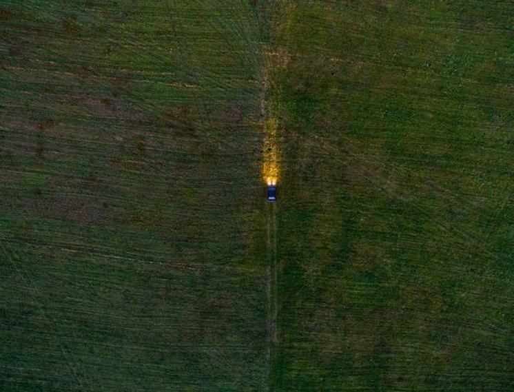 Автомобиль проезжает поле в Кусе, Челябинская область, Россия