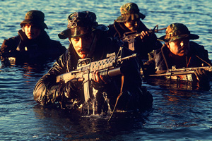 U.S. Navy Sea-Air-Land (SEAL) members emerge from the water during tactical warfare training.  The SEAL member in the foreground is armed with an M-16A1 rifle equipped with an M203 grenade launcher.  The SEAL member on the right is armed with an HK-33KA1 rifle.