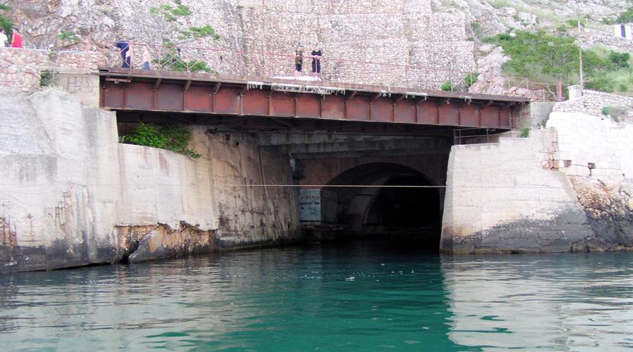 База подводных лодок Во времена СССР это место обозначалось на секретных картах только как «объект 825 ГТС». Именно здесь, неподалеку от Балаклавы располагалась база подводных лодок. Объект был построен еще в 1961 году, в рамках программы по усилению противоатомной защиты страны. Попасть внутрь можно только через штольню или с северной части горы Таврос, причем обе двери имели тщательную маскировку и были водонепроницаемыми. Территория базы занимала целых 5100 квадратных метров: собственный госпиталь, своя пекарня и даже свой спортивный центр. В случае нападения на страну потенциального противника, на базе с легкостью разместилось бы все население Балаклавы, а припасов хватило бы на целых три года.