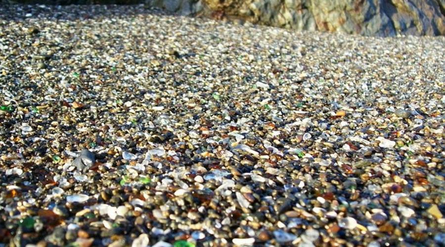 Стеклянный пляж На побережье Северной Калифорнии расположен один из самых необычных пляжей мира. Он практически полностью покрыт кусочками разноцветного стекла и называется Sea Glass Beach. Вообще-то, в середине XX века на месте пляжа обреталась самая настоящая свалка, которую местные жители взяли и подожгли. Сгорело все, а стекло просто оплавилось. Море превратило острые осколки в гладкие, и теперь пляж считается местной достопримечательностью.