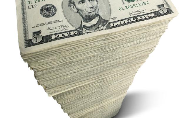 Stack of five-dollar bills on white background