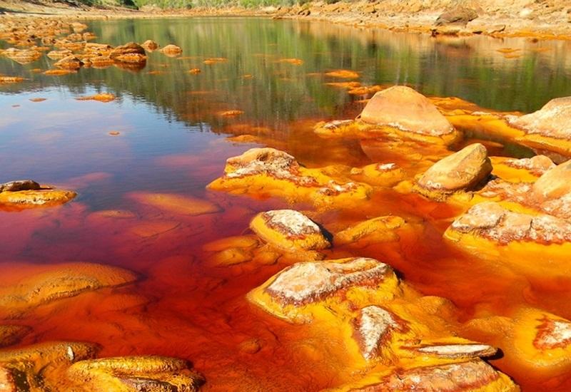 Рио Тинто, Испания Рио – река, Тинто – красная. Бразилию в свое время так назвали португальские колонизаторы по местному именованию красного дерева. Испанская провинция Андалусия до сих пор находится в Европе. Беда в том, что более трех тысяч лет там добывают золото, серебро, медь, никель, молибден… В средние века добывали еще и ртуть. Результат загрязнения озера, в которое впадают многочисленные стоки, предсказуем и виден на иллюстрации. Как ни странно, там живут бактерии-экстремалы, которым не нужен воздух (они анаэробные), но очень нужен азот. Астробиологи полагают, что этот вид бактерий неплохо приживется и на Марсе.