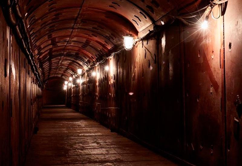 Бункер-42 На Таганке стоит неприметный двухэтажный особняк. На первом этаже нет окон – дом построен для того, чтобы скрыть бетонный купол толщиной шесть метров, закрывающий шахту, уходящую вглубь на 60 метров. Там, на уровне кольцевой линии метро, находятся четыре тоннеля, соединенные переходами. Это запасной командный пункт Дальней авиации. Сейчас здесь музей холодной войны. Попасть в него можно, спустившись по лестнице из 310 ступеней с обратным отсчетом этажей, любуясь обшитыми стальными пластинами коридорами с массивными герметичными дверями. В конце увлекательной экскурсии гаснет свет, появляется дым, включается красное аварийное освещение, и по внутренней связи объявляют, что по столице нанесен ядерный удар.