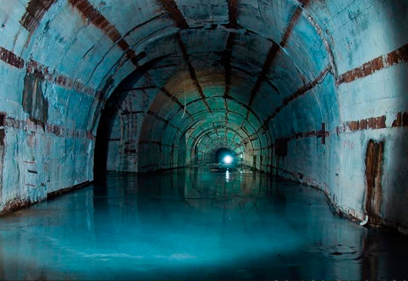 Укрытие подлодок Под землей можно хранить даже то, что плавает. Одно из самых грандиозных сооружений времен Холодной войны – укрытие подводных лодок в Балаклаве. Гора Таврос, в недрах которой оно расположено, состоит из очень прочного мраморовидного известняка, а толщина породы под тоннелями и каналами – более 100 метров. Объект имеет первую категорию противоатомной устойчивости – ему не страшно прямое попадание бомбы мощностью 100 килотонн.